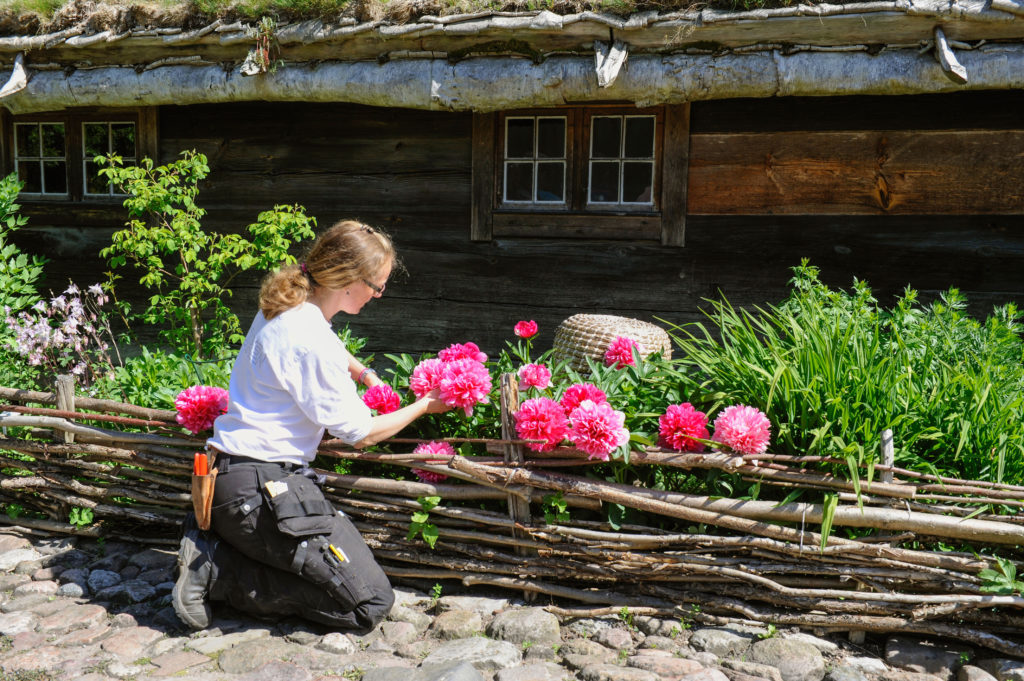 A gardener tends to to flowers outside The Blekinge Farmhouse.