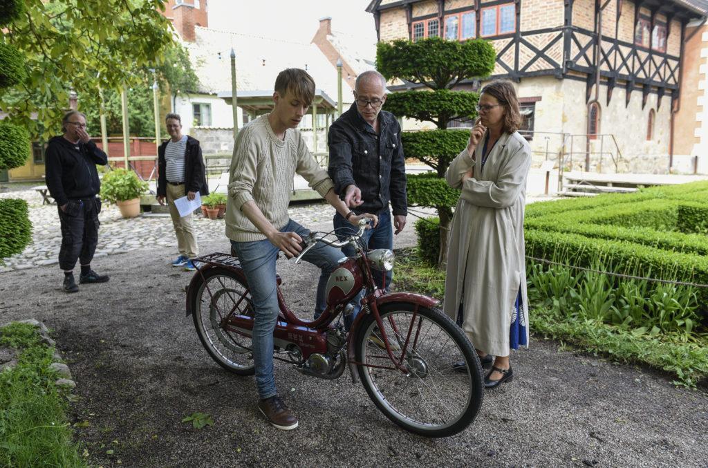 Intendent Niklas Ingemarsson (i mitten) visar pedagogerna Olle Ekström och Kristina Bakran hur de ska starta Rexmopeden.